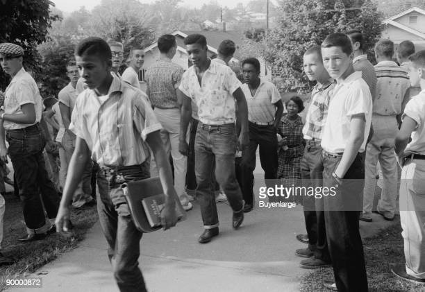 African American boy walking through a crowd of white boys during a period of violence related to school integration