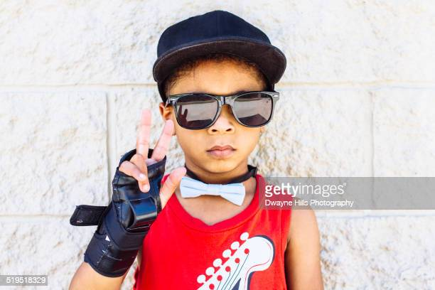African American boy wearing bow tie, wrist brace, sunglasses and baseball cap