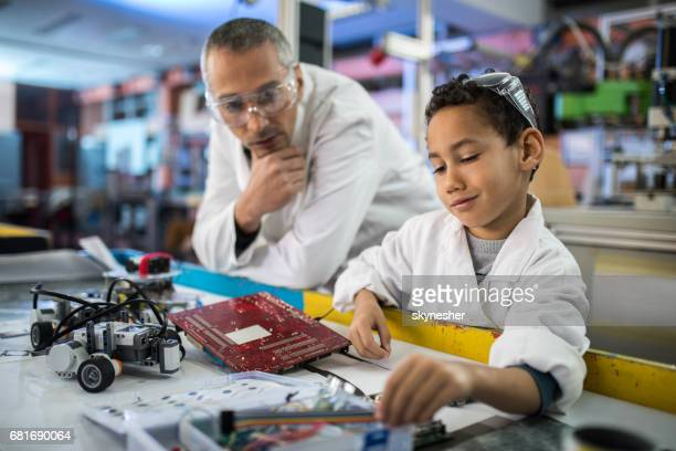 African American boy working on a computer part with a surveillance of his teacher.