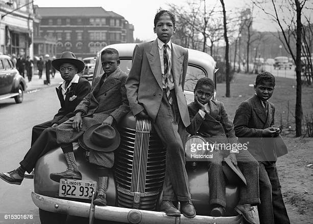 African American boys sit on the front of a car in their Sunday best on Easter morning in their South Side Chicago neighborhood