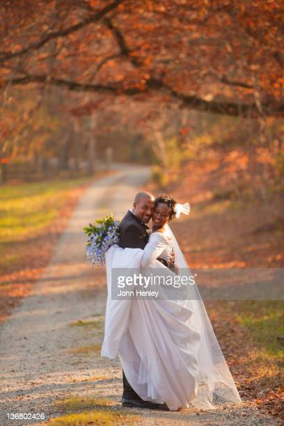 African American bride and groom hugging on path