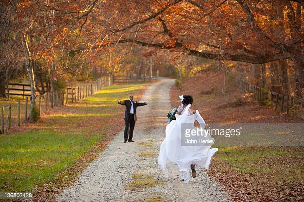African American bride and groom running to each other on path