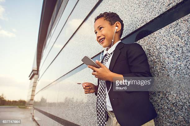 African American business boy listening music on his cell phone.