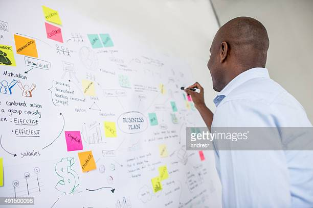 African American business man drawing a plan