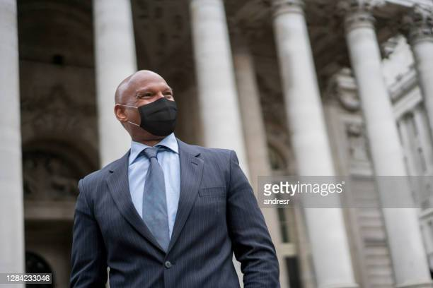 african american business man wearing a facemask outside an office building - courthouse stock pictures, royalty-free photos & images