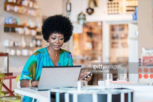 african american business owner using laptop in store - afro americano foto e immagini stock