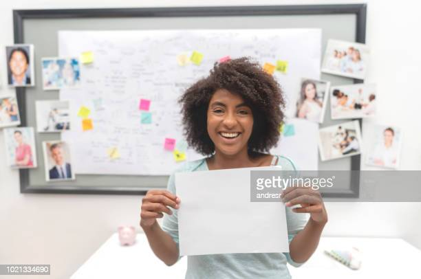 African American business woman brainstorming at a creative office and holding a blank document