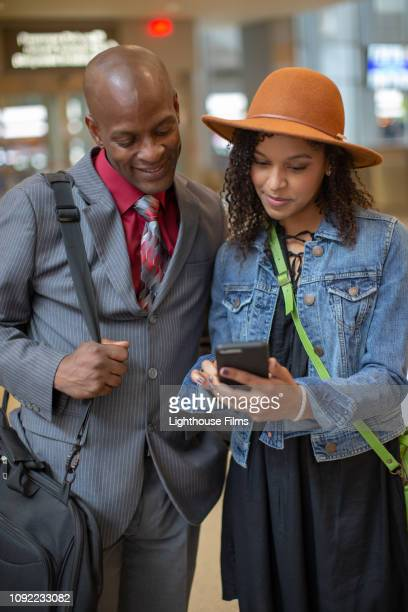african american businessman and hip young mixed race woman look at smartphone in airport lobby. - stranger stock pictures, royalty-free photos & images
