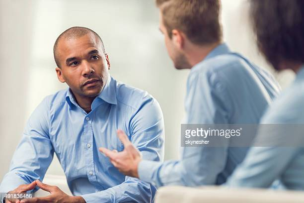 African American businessman discussing with his colleagues.