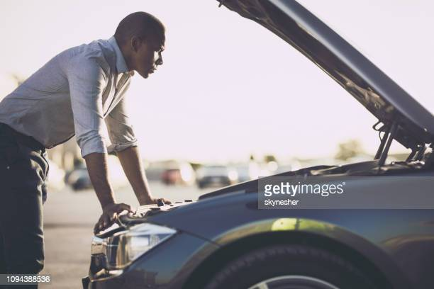 african american businessman examining his care after breakdown. - broken down car stock pictures, royalty-free photos & images