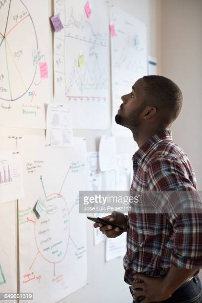 African American businessman examining papers in office