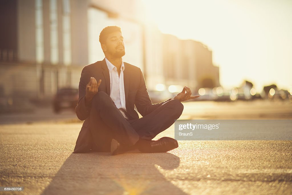 African American businessman in Lotus position at sunset. : Stock Photo
