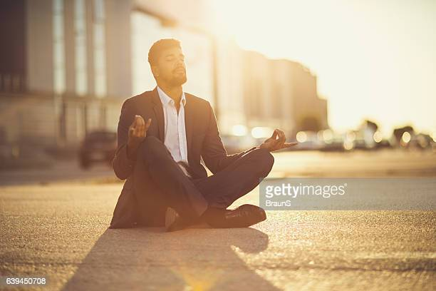 African American businessman in Lotus position at sunset.
