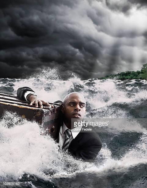 African American businessman in ocean holding trunk