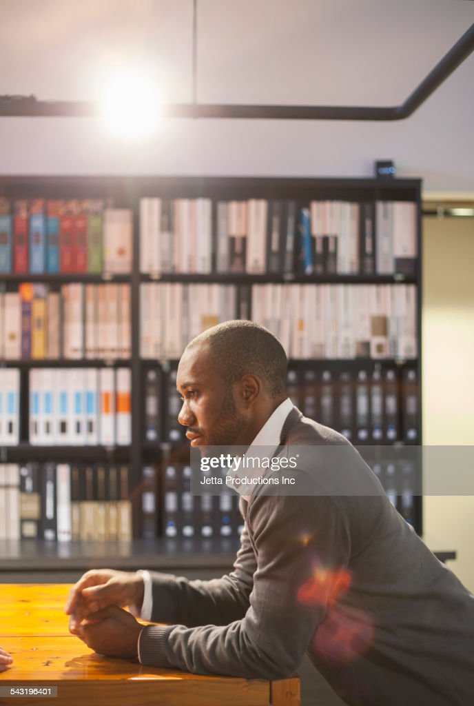 African American businessman leaning on table in office : Stock Photo