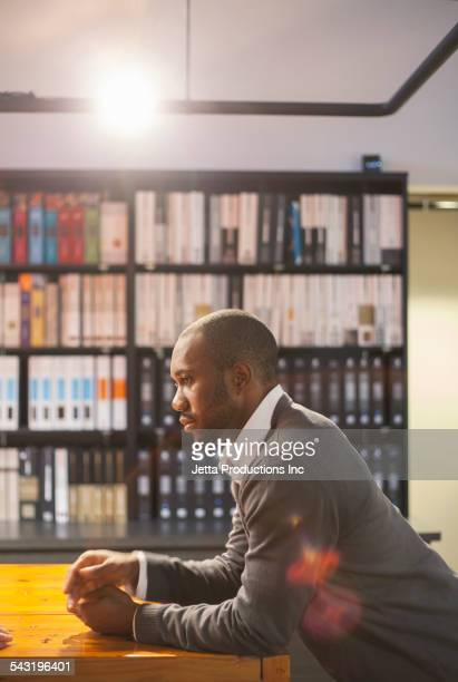 African American businessman leaning on table in office