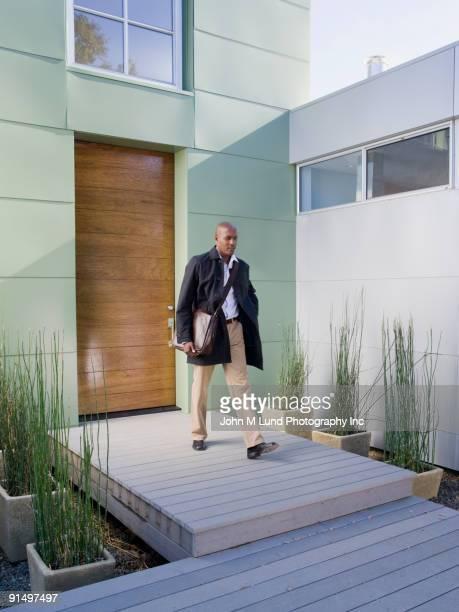 African American businessman leaving house