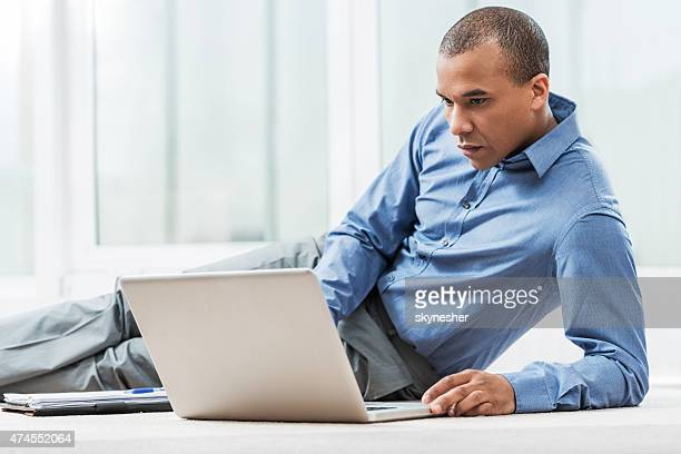 african american businessman lying on floor and using laptop. - one mid adult man only stock pictures, royalty-free photos & images
