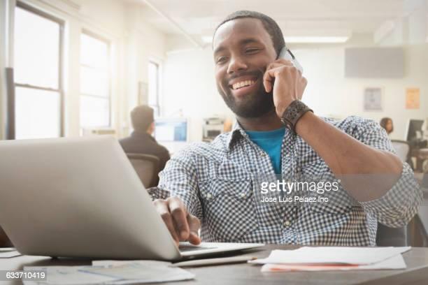 african american businessman multitasking in office - persona in secondo piano foto e immagini stock