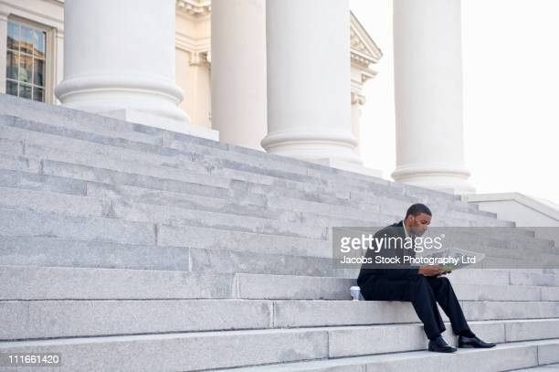 African American businessman reading newspaper on steps of courthouse