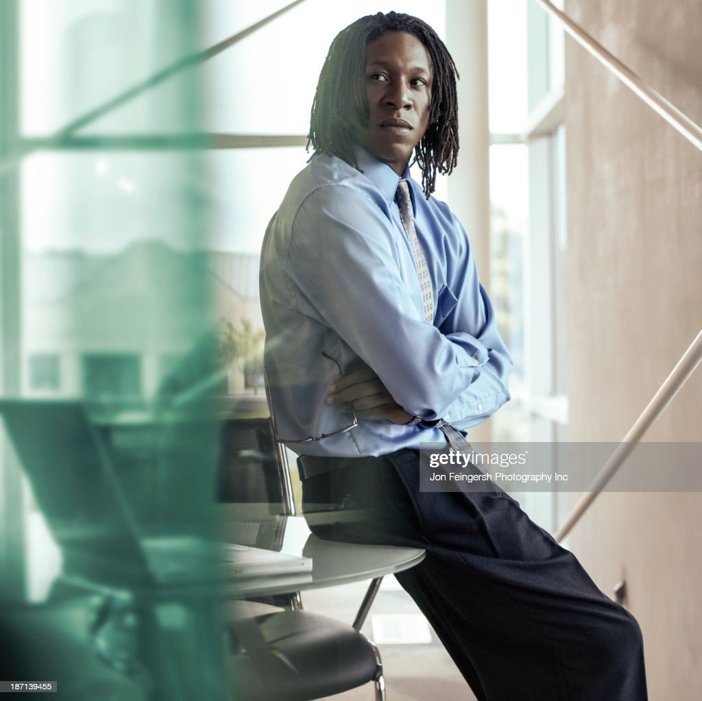 African American businessman sitting on desk : Stock Photo