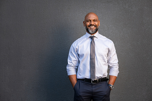 African american businessman smiling on grey 1138563417