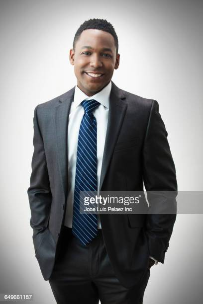 african american businessman smiling with hand in pockets - black suit stock pictures, royalty-free photos & images