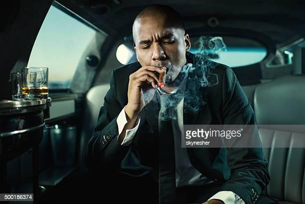 African American businessman smoking Cuban cigar in limousine.