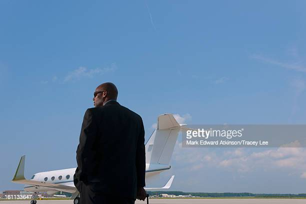 African American businessman standing on airport tarmac