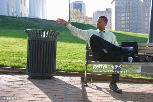 African American businessman throwing trash in garbage can