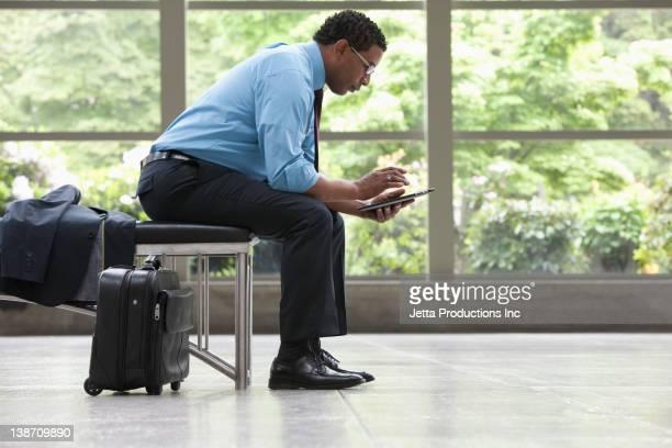 African American businessman using digital tablet in lobby