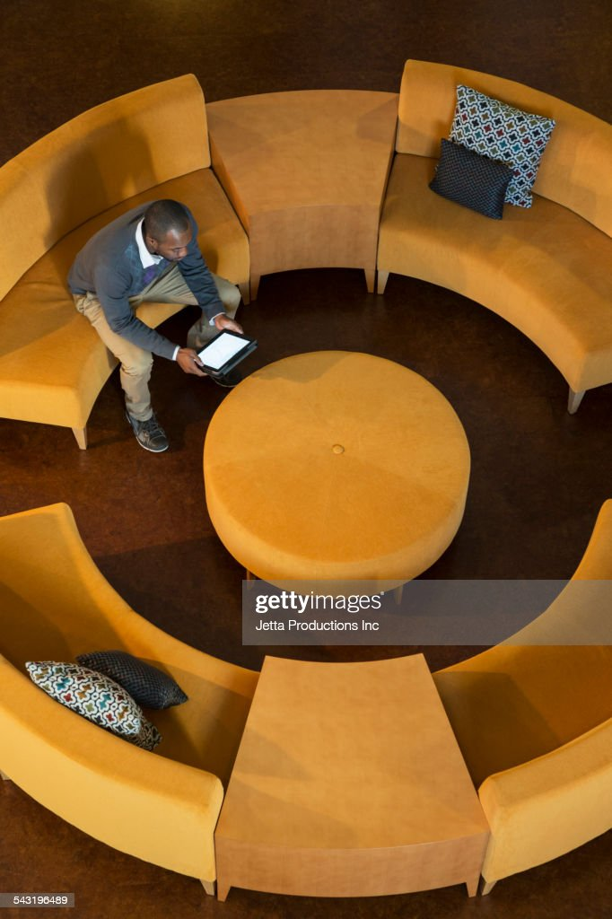 African American businessman using digital tablet on circular sofa : Stock Photo