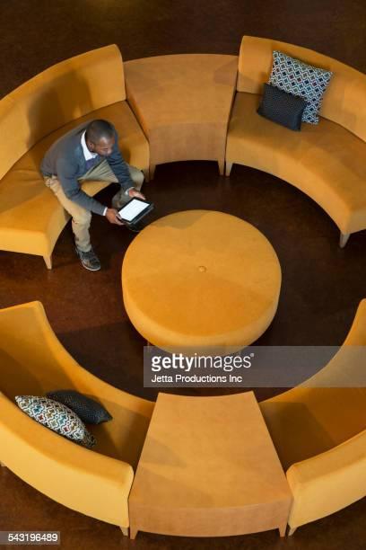 African American businessman using digital tablet on circular sofa