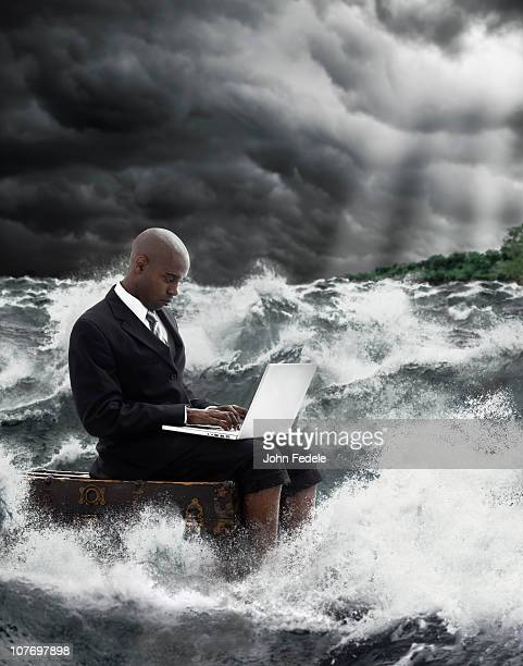 African American businessman using laptop in stormy sea