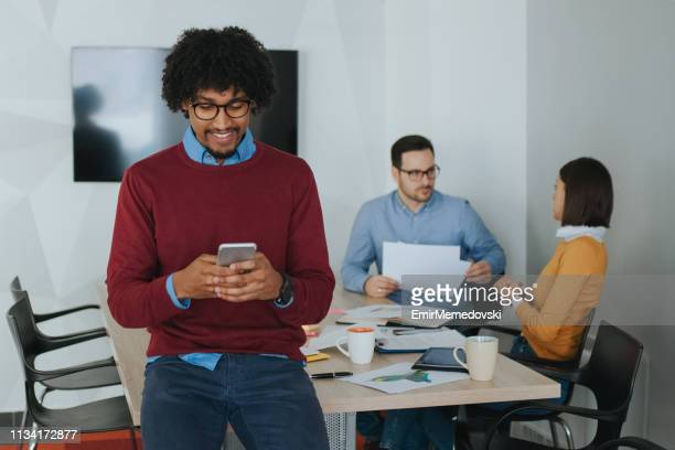 African American businessman using mobile phone during coffee break