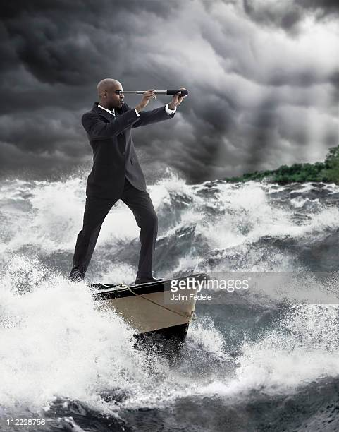 African American businessman using telescope on boat