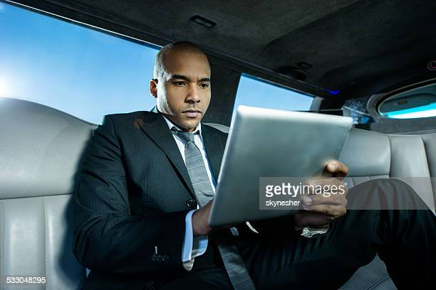 African American businessman using touchpad in a limousine.