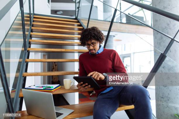 African American businessman working on the stairs