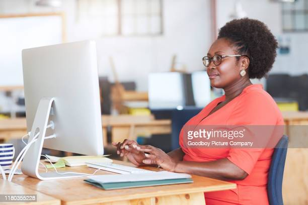 african american businesswoman at work in a large office - large build stock pictures, royalty-free photos & images