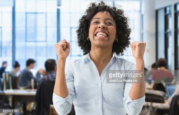 African American businesswoman cheering in office