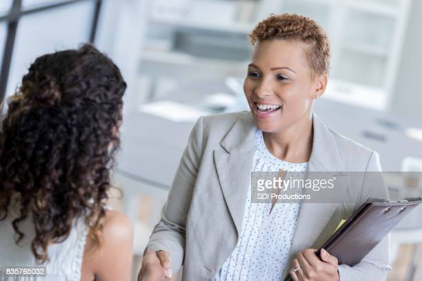 african american businesswoman greets client - assistant stock pictures, royalty-free photos & images