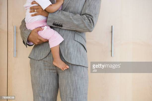 African American businesswoman holding baby