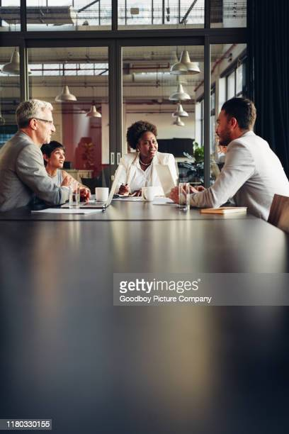 african american businesswoman listening to her team discussing work - diversità foto e immagini stock