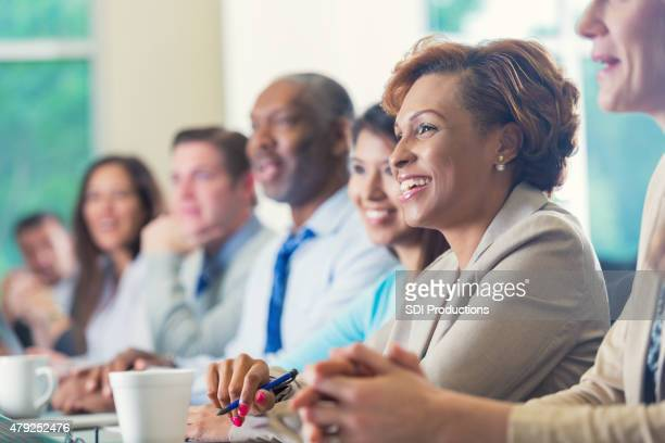 African American businesswoman listening to seminar speaker at business conference