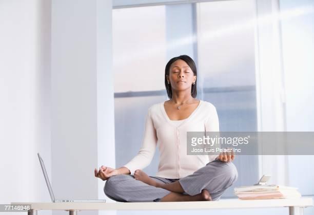 African American businesswoman meditating on desk