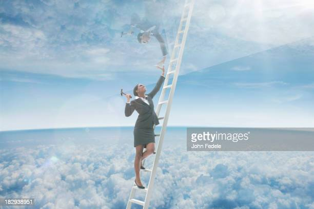 African American businesswoman on ladder to glass ceiling