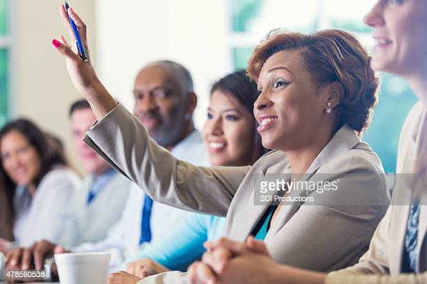 african american businesswoman raising hand, asking question in business conference - adult stock pictures, royalty-free photos & images