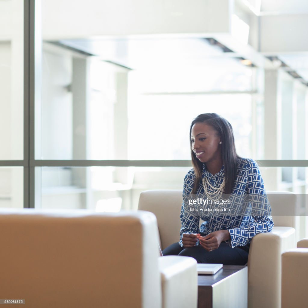 African American businesswoman sitting in office lobby : Stock Photo