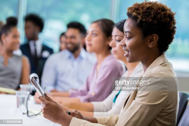 african american businesswoman takes notes during meeting - town hall meeting stock pictures, royalty-free photos & images