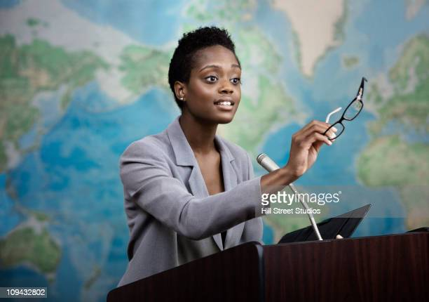 african american businesswoman talking at podium - persuasion stock pictures, royalty-free photos & images